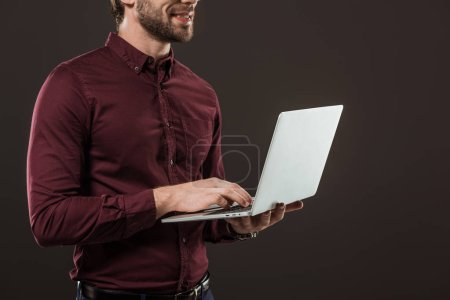 cropped shot of smiling man using laptop isolated on black