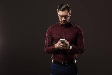 Photo pour Homme sérieux dans les lunettes en utilisant smartphone isolé sur noir - image libre de droit