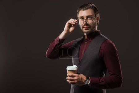 Photo for Stylish businessman with coffee to go adjusting eyeglasses and looking at camera isolated on black - Royalty Free Image