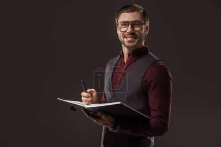 handsome buisnessman in eyeglasses taking notes and smiling at camera isolated on black