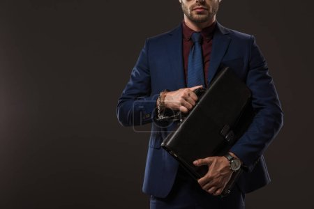 cropped shot of businessman in handcuffs holding briefcase isolated on black