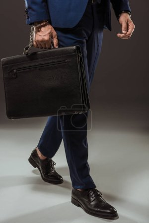 cropped shot of businessman in handcuffs with briefcase on black