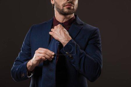 cropped shot of stylish businessman adjusting necktie isolated on black