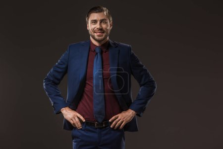 handsome businessman standing with hands on waist and smiling at camera isolated on black