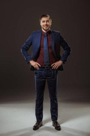 Foto de Vista de la longitud total de apuesto hombre de negocios de pie con las manos en la cintura y sonriendo a cámara en negro - Imagen libre de derechos