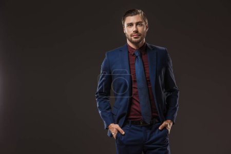 handsome businessman in stylish suit standing with hands in pockets and looking at camera isolated on black