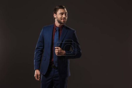 handsome smiling businessman in suit looking away isolated on black