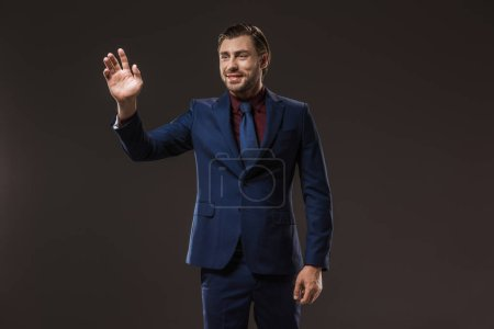 smiling businessman waving hand and looking away isolated on black