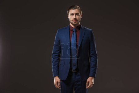 portrait of handsome businessman in suit standing and looking at camera isolated on black