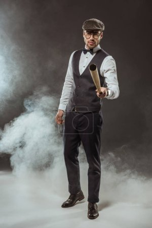 serious stylish man in bow tie and cap holding baseball bat while standing in smoke