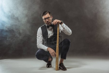 serious stylish man in eyeglasses crouching with baseball bat and looking at camera on black