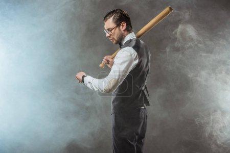 side view of stylish businessman holding baseball bat and checking wristwatch in smoke