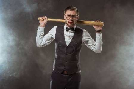 handsome serious man holding baseball bat and looking at camera while standing in smoke