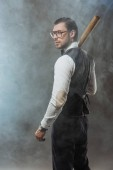 handsome man in bow tie and eyeglasses holding baseball bat and looking away in smoke