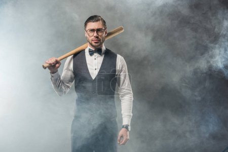 stylish man in bow tie and eyeglasses holding baseball bat and looking at camera in smoke