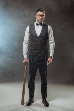 full length view of stylish man in bow tie and eyeglasses holding baseball bat and looking at camera in smoke