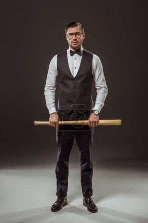 full length view of stylish man in bow tie and eyeglasses holding baseball bat and looking at camera on black