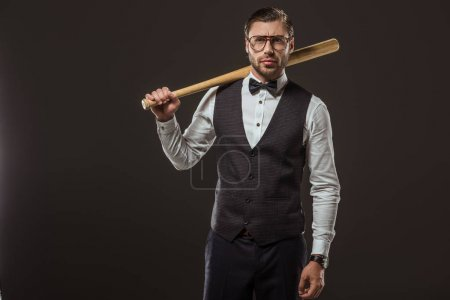 stylish man in bow tie and eyeglasses holding baseball bat and looking at camera isolated on black