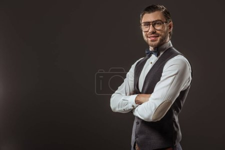 portrait of handsome stylish man in bow tie and eyeglasses standing with crossed arms and smiling at camera isolated on black