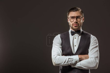 handsome stylish man in bow tie and eyeglasses standing with crossed arms and looking at camera isolated on black
