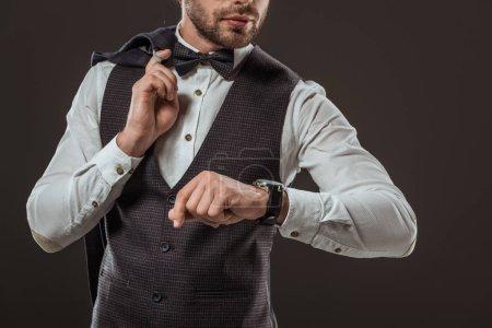 Photo pour Photo recadrée d'élégant homme tenant costume veste et vérification montre-bracelet isolée sur fond noir - image libre de droit