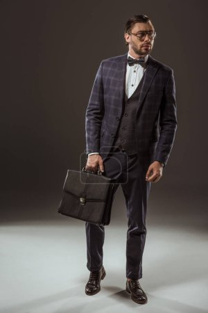 full length view of businessman holding briefcase and looking away on black