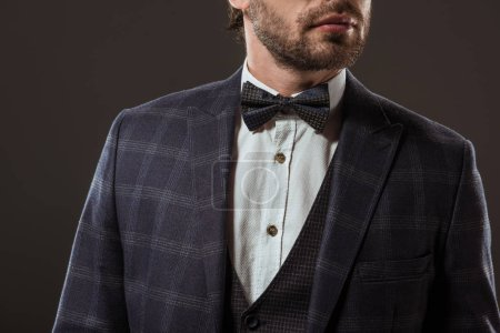 cropped shot of stylish man wearing suit and bow tie isolated on black