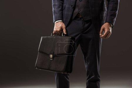 cropped shot of businessman holding briefcase on black