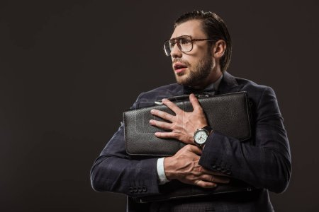 scared buisnessman in eyeglasses hugging briefcase and looking away isolated on black