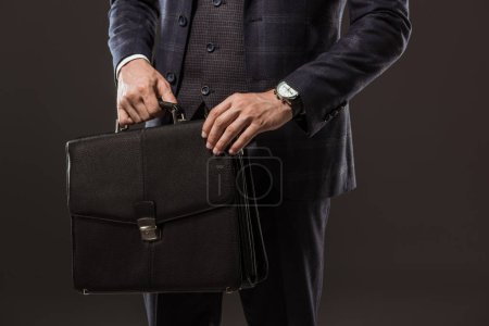 cropped shot of businessman holding briefcase isolated on black