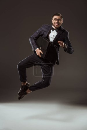excited businessman with briefcase jumping and looking at camera on black
