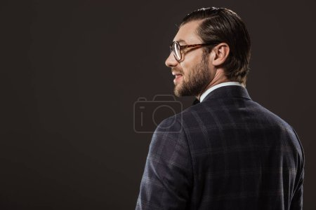 back view of handsome smiling man in eyeglasses looking away isolated on black