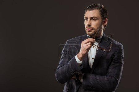 handsome man in suit and bow tie holding eyeglasses and looking away isolated on black