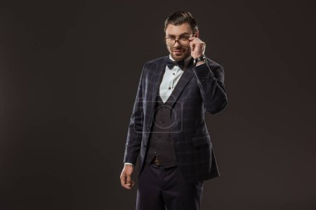 portrait of handsome smiling man in suit and bow tie adjusting eyeglasses isolated on black