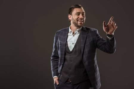 handsome smiling businessman waving hand and looking away isolated on black
