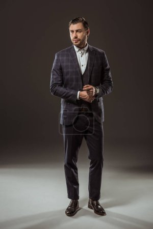 full length view of handsome businessman in stylish suit looking away on black