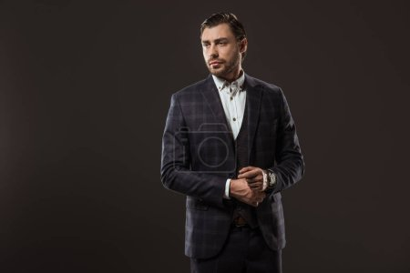 Photo for Handsome stylish young businessman looking away isolated on black - Royalty Free Image