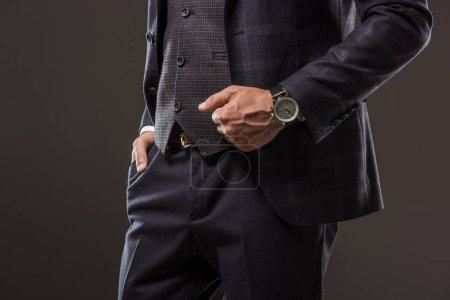 Photo for Cropped shot of man in stylish suit wearing wristwatch and standing with hand in pocket isolated on black - Royalty Free Image
