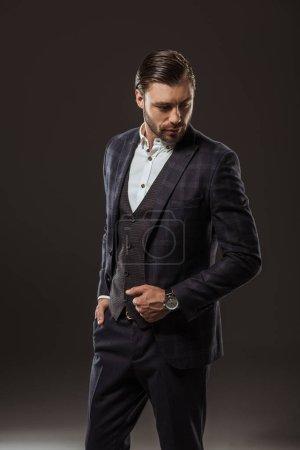 Photo pour Beau jeune homme élégant en costume regardant vers le bas sur fond noir - image libre de droit