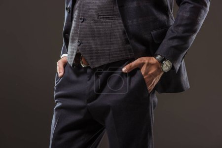 cropped shot of stylish businessman standing with hands in pockets isolated on black