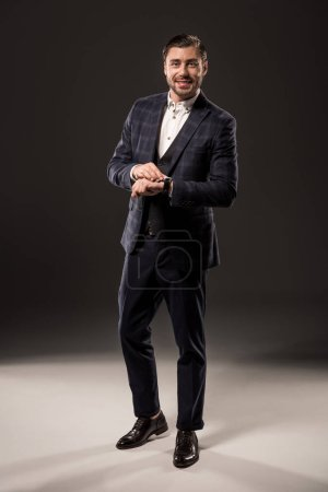 Photo for Full length view of stylish businessman checking wristwatch and smiling at camera on black - Royalty Free Image