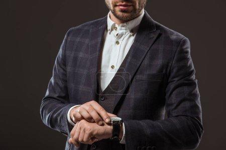 Foto de Toma recortada de elegante empresario control reloj aislado en negro - Imagen libre de derechos