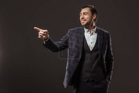 handsome smiling businessman pointing with finger and looking away isolated on black