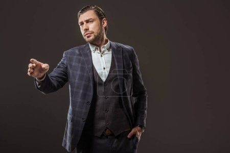 handsome stylish man pointing with finger and looking away isolated on black