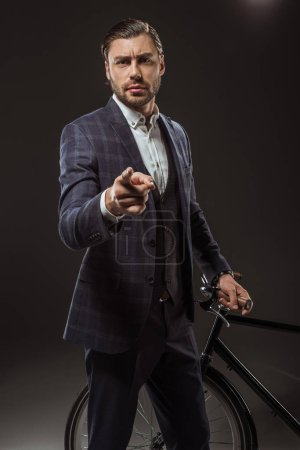 serious young man in suit pointing with finger and looking at camera while standing near bicycle on black