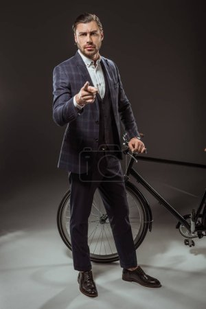 serious young man in suit pointing at camera while standing near bicycle on black