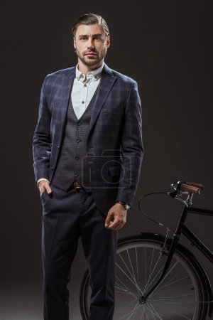 handsome young man in suit looking at camera while standing near bicycle on black