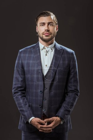 portrait of handsome stylish man in suit looking at camera isolated on black