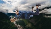 businessman in eyeglasses with baseball glove flying in clouds above amazing natural landscape