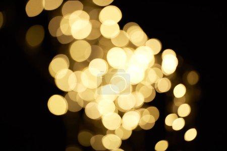 beautiful shiny defocused golden bokeh on black background